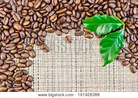 Frame of black coffee beans with green leaves on brown coarse woven fabric