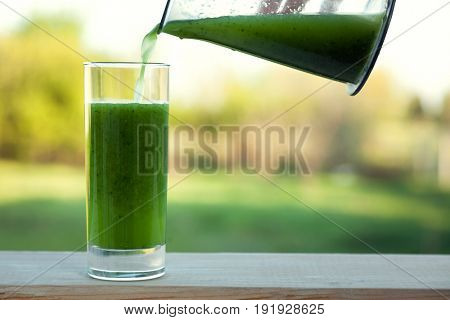 Smoothies green dietary vegetarian on a wooden table with a mint leaf