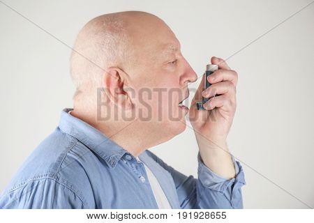 Senior man using asthma inhaler on light background