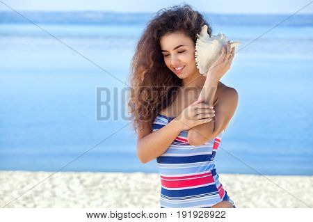 A young attractive girl in a colorful striped swimsuit holds a large white shell on the beach by the sea.