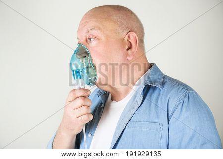 Senior man using asthma machine on light background