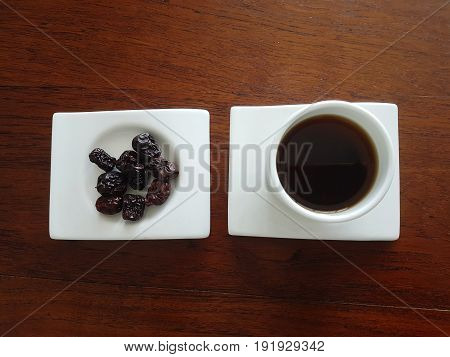 High angle view of healthy Chinese Red dates tea drink and whole fruit served on white plate and cup for promotion of health and complexion, set on wooden table.