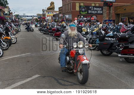 Sturgis South Dakota - August 8 2014: Rider in the main street of the city of Sturgis in South Dakota USA during the annual Sturgis Motorcycle Rally