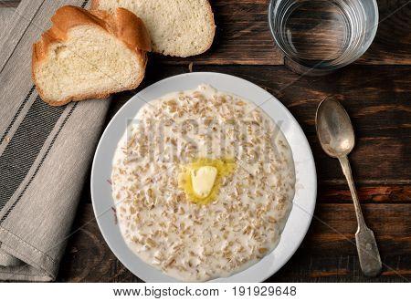 Top view of oatmeal porridge in bowl on dark wood background