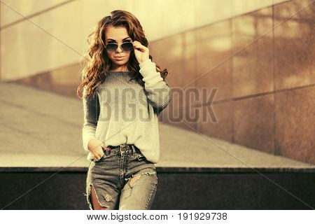 Happy young woman in sunglasses walking in city street. Stylish fashion model in pullover and ripped jeans outdoor