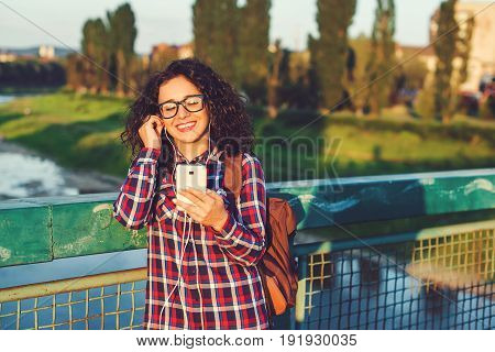 Smiling Young Woman Or Teenage Girl With Smartphone And Headphones Listening To Music Outdoors.