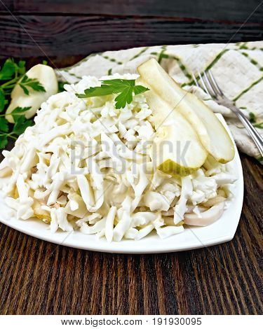 Salad of squid, rice, pears and eggs in a plate, parsley, napkin and fork on a dark wooden board