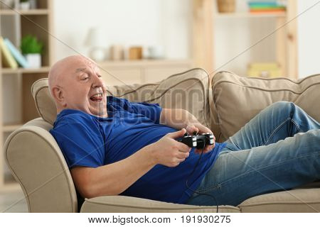 Fat senior man playing videogame while lying on sofa at home. Sedentary lifestyle concept