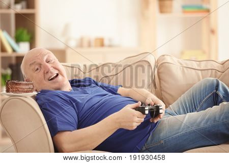 Fat senior man with videogame console and cake lying on sofa at home. Sedentary lifestyle concept