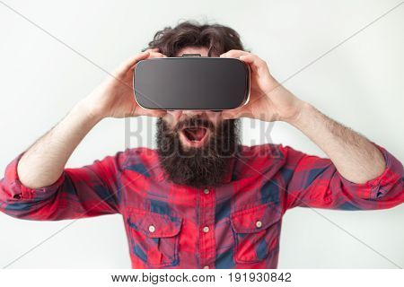 Young bearded man looking amazed while wearing VR headset on white background.