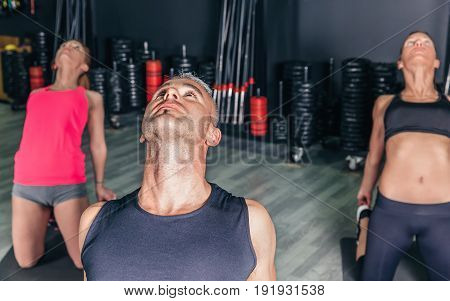 Close up of young man stretching body in fitness class on sports center