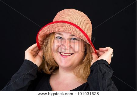 Portrait of a happy attractive european light overweighted red haired female posing with a red hat - studio shot on black background