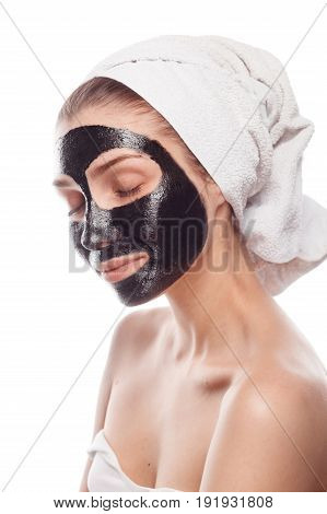 Woman after shower with towel on head posing with black cleansing mask on face keeping eyes closed.