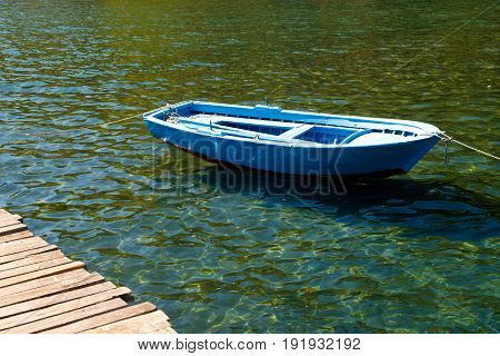 An old boat near a wooden bridge on a beautiful lake. Fishing boat on the pier