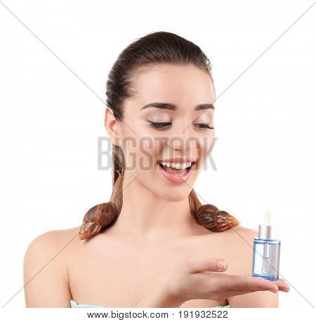 Beautiful young woman with giant Achatina snails and cosmetic product on white background