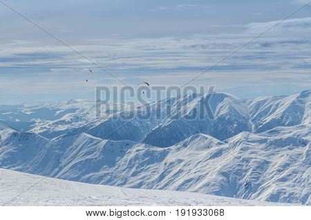 Winter mountains panorama with snow on tops of rocks and flying paragliders
