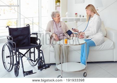 Young nurse measuring blood pressure of disabled elderly woman at home