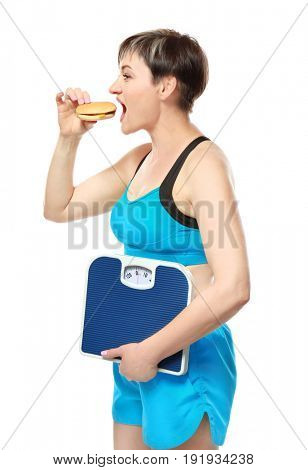 Mature woman with scales and hamburger on white background. Weight loss concept