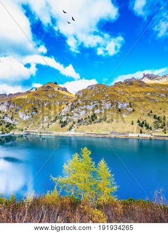Magnificent lake Lago di Fedaia in the Dolomites. The concept of ecological and extreme tourism. Cloudy cold autumn day