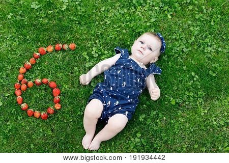 Adorable baby girl on grass wearing blue clothes and headband with strawberries for 6 moths. Cute little child laughing and smiling.