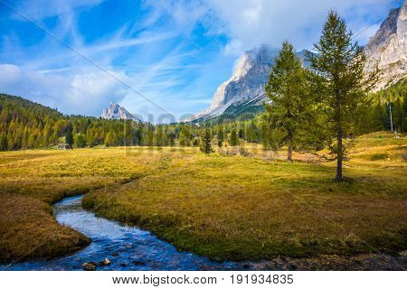 The concept of ecological and extreme tourism. Cold fast spring flows through the valley. The dizzying Dolomites. Sharp rocks surround the grassy valleys