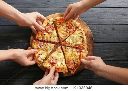 Hands taking pizza slices from wooden plate, close up view