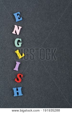 English word on black board background composed from colorful abc alphabet block wooden letters, copy space for ad text. Learning english concept