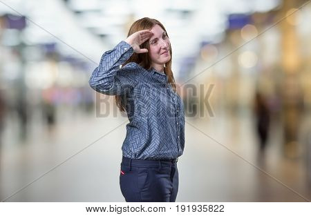 Pretty Business Woman Saluting Over Blur Background
