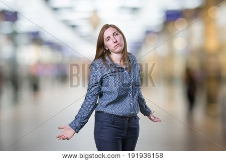 Pretty young businesswoman is overwhelmed over blur background.