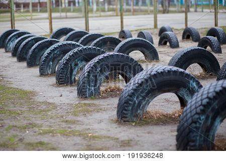 Wheels dug into the ground at the school stadium. Arrangement of children's playgrounds.