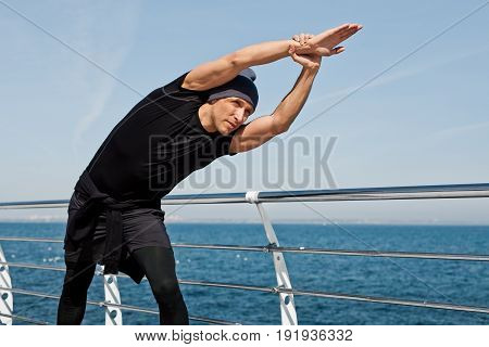 Young man in hat and sportswear stretching hands on pier with sea on background in sunny day.