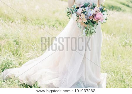 fine art wedding photography. Beautiful bride with bouquet and dress with train in the nature