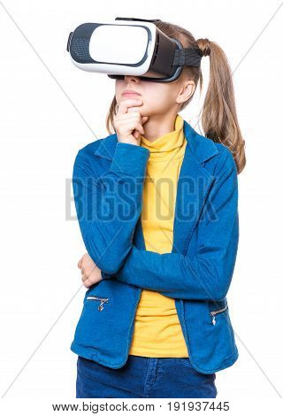 Thoughtful little girl wearing virtual reality goggles watching movies or playing video games, on white. Casual thinking kid looking in VR glasses. Emotional portrait of child experiencing 3D gadget