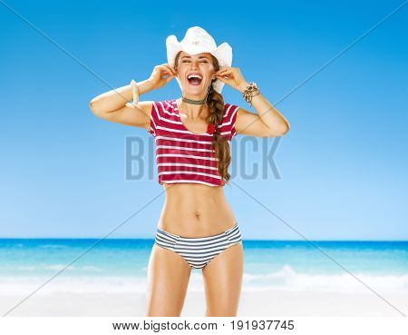 Perfect summer. smiling healthy woman on the beach listening to the music with headphones