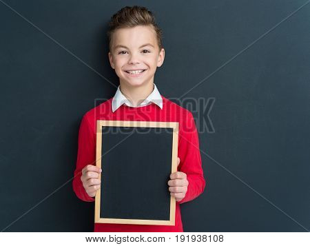 Portrait of cute smiling teen boy with small blackboard at the black chalkboard in classroom.