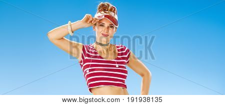 Perfect summer. Portrait of smiling young woman in red sun visor on the seacoast