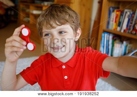 School kid playing with Tri Fidget Hand Spinner indoors. and making selfie with smartphone. summer trend of 2017. red hand spinner, fidgeting toy rotating on child's hand