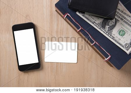 Top view of credit card and smart phone with white blank screen on wood desktop.