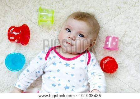 Cute adorable newborn baby playing with colorful educational rattle toy. New born child, little girl. Family, new life, childhood, beginning concept. Baby learning grab