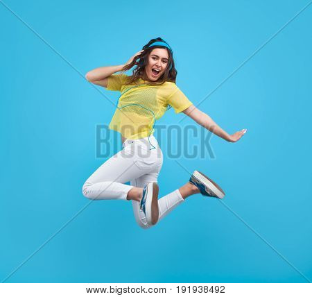 Side view of young stylish girl in motion of jumping while wearing big headphones.