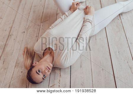 Sexy blonde woman in a grey sweatshirt lies on the wooden floor. Mock-up.