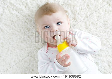 Cute adorable ewborn baby girl holding nursing bottle and drinking formula milk. First food for babies. New born child, little girl laying on white background. Family, new life, childhood, bottle-feeding concept.