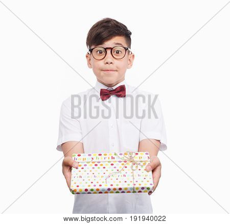 Adorable boy in glasses and bowtie outstretching hands with wrapped giftbox on white background.