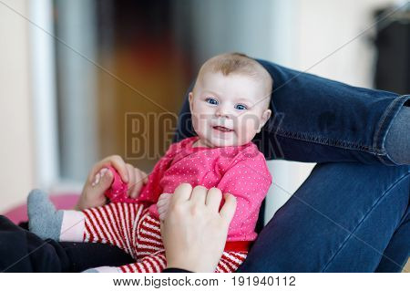 father having fun with newborn baby daughter, family portrait together. Baby girl on dad legs, love. Happy child looking on dad. Bonding, family, new life