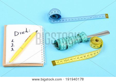 Tapes for measuring in different colors metal fork and notebook with pen on it and diet plan isolated on light blue background