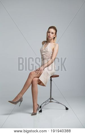 Side view of woman in short elegant dress and high heels posing on chair in studio.