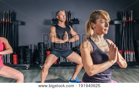 Portrait of blonde woman stretching body in fitness class on sports center