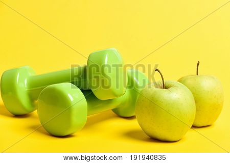 Pairs Of Green Dumbbells And Fresh Apples