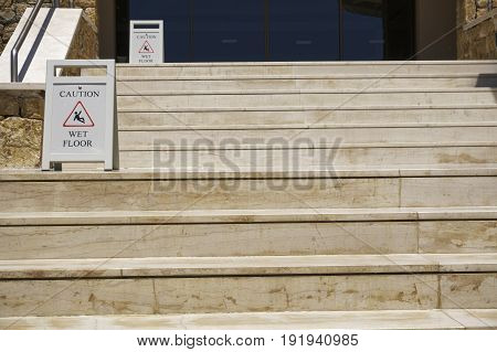 Caution wet floor warning signs on stairs. Staircase with slippery when wet signs.