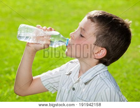 Child drinking water. Boyl outdoors